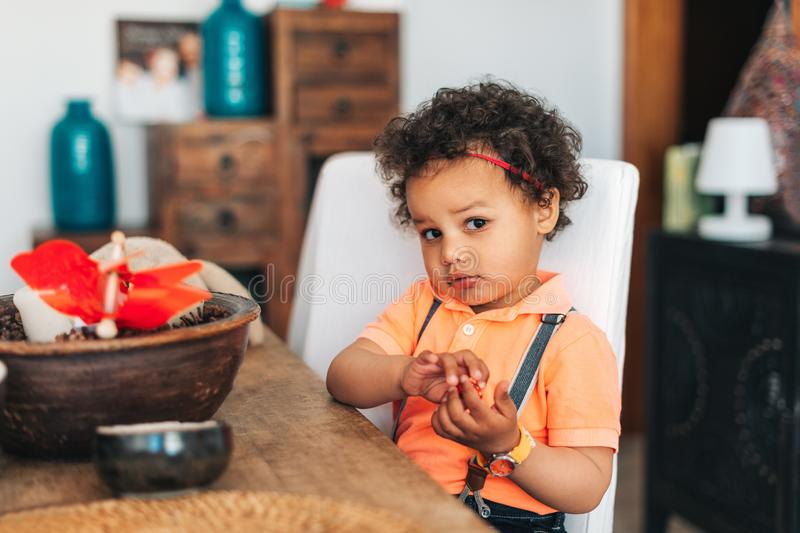 Portrait of adorable african kid boy sitting at the table stock image