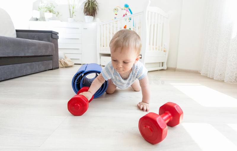 Portrait of adorable baby exercising with dumbbells on floor at. Portrait of adorable baby boy exercising with dumbbells on floor at living room royalty free stock photo