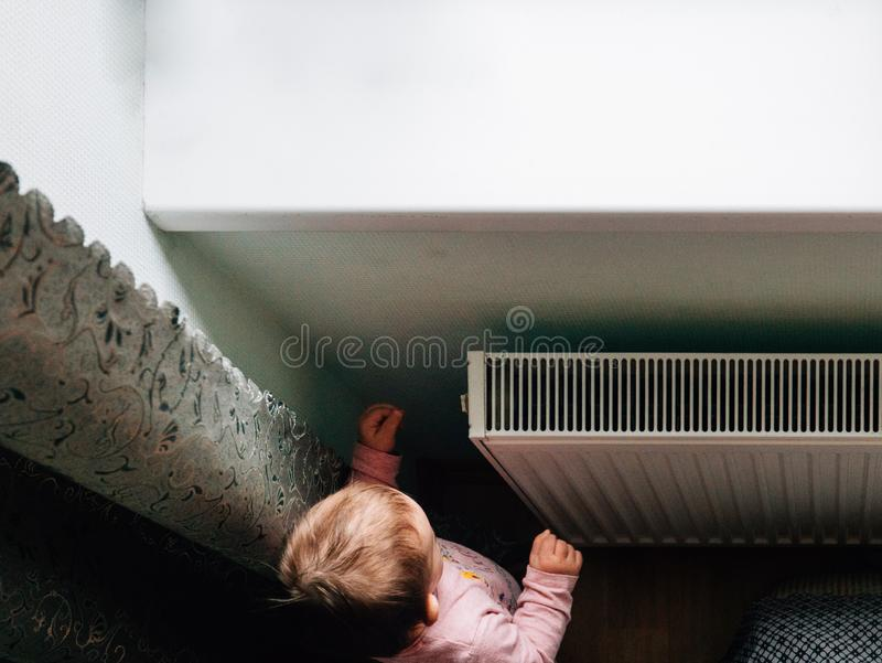 Portrait of an adorable baby near the radiator at home utilities concept stock photos