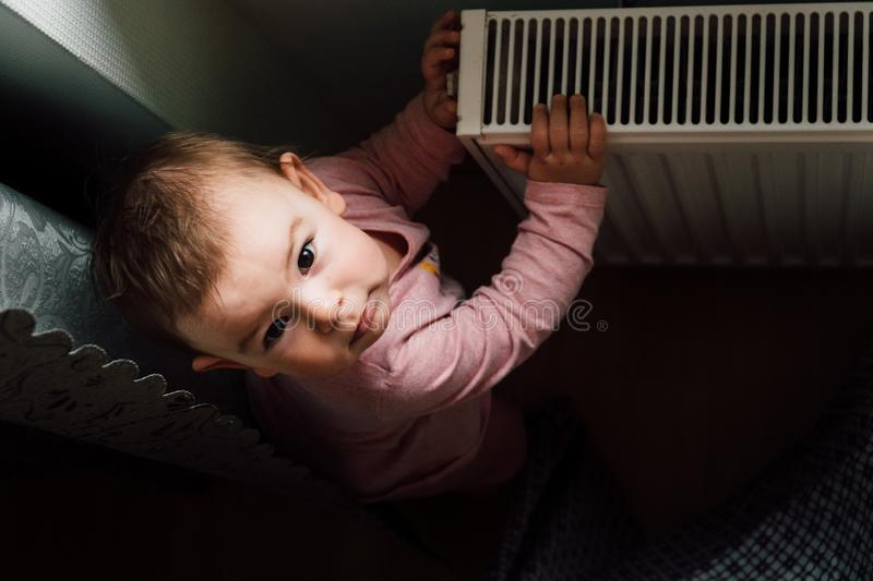 Portrait of an adorable baby near the radiator at home utilities concept royalty free stock photos