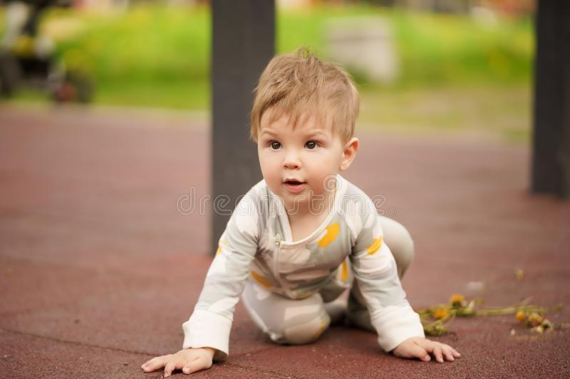 Portrait of adorable baby playing at playground. Concept: family values. Portrait of adorable innocent funny brown-eyed baby playing at outdoor playground royalty free stock photo
