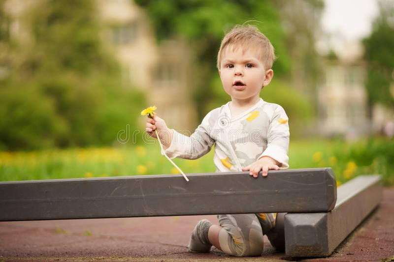 Portrait of adorable baby playing at playground. Concept: family values. Portrait of adorable innocent funny brown-eyed baby playing at outdoor playground stock images