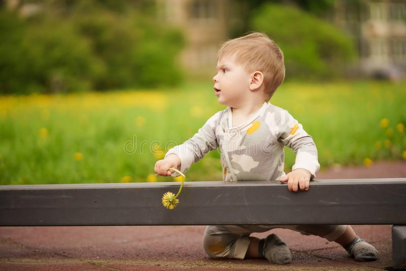 Portrait of adorable baby playing at playground. Concept: family values. Portrait of adorable innocent funny brown-eyed baby playing at outdoor playground stock photography