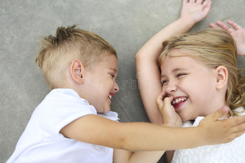 Portrait of adorable brother and sister smile and laugh together outdoors stock photo