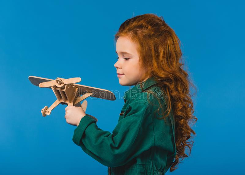 portrait of adorable child in pilot costume with wooden plane toy stock photography
