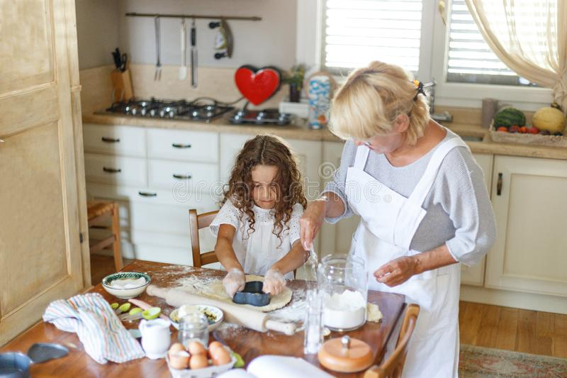 Adorable curly little girl with her grandmother cooking together at kitchen table. helps grandma in the kitchen. stock photo