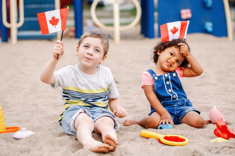 Caucasian boy and latin hispanic baby girl holding waving Canadian flags. Multiracial children celebrating Canada Day stock photo
