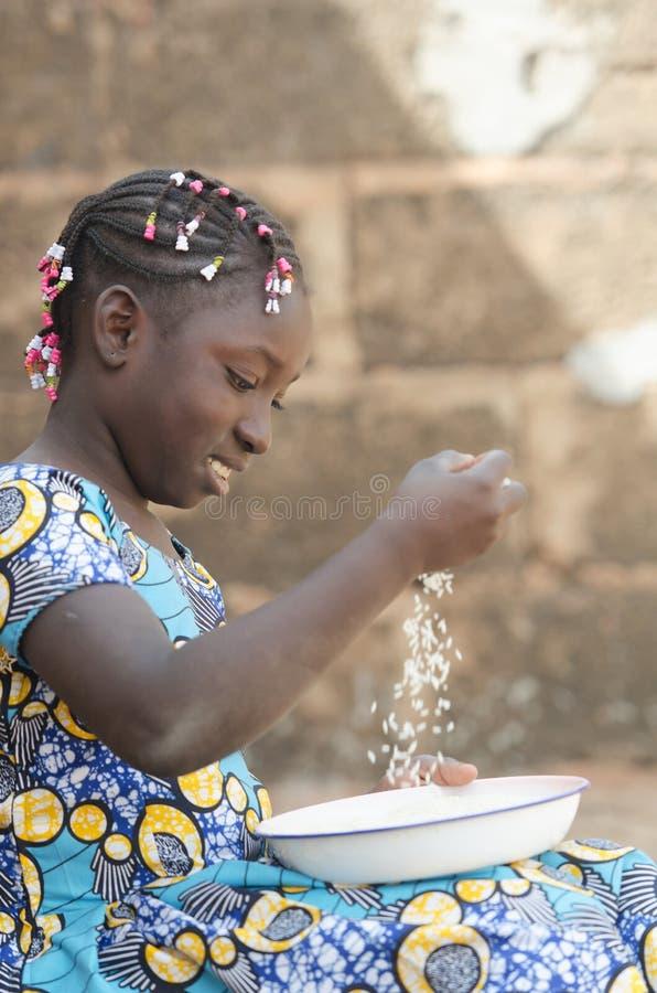 Portrait adorable de la petite fille africaine préparant le riz pour le repas photographie stock libre de droits
