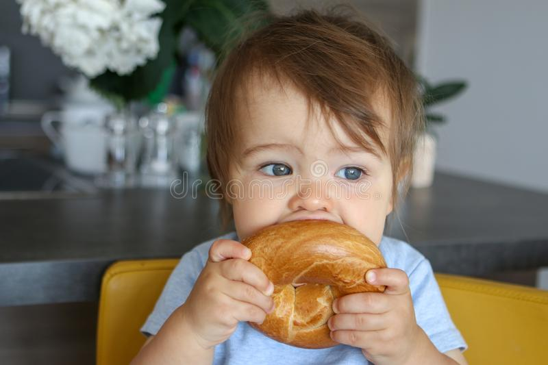 Portrait of adorable funny baby boy holding and biting big bagel sitting on yellow chair at home kitchen. Close-up stock photography