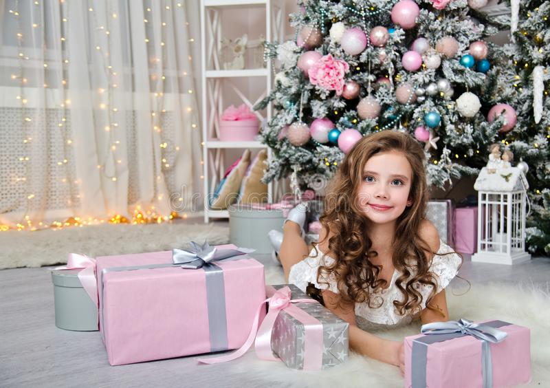 Portrait of adorable happy smiling little girl child in princess dress with gift boxes lying near fir tree stock photos