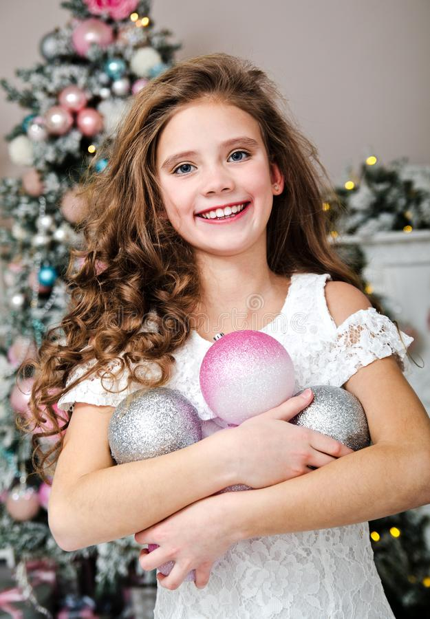 Portrait of adorable happy smiling little girl child in princess dress holding christmas balls near fir tree stock images