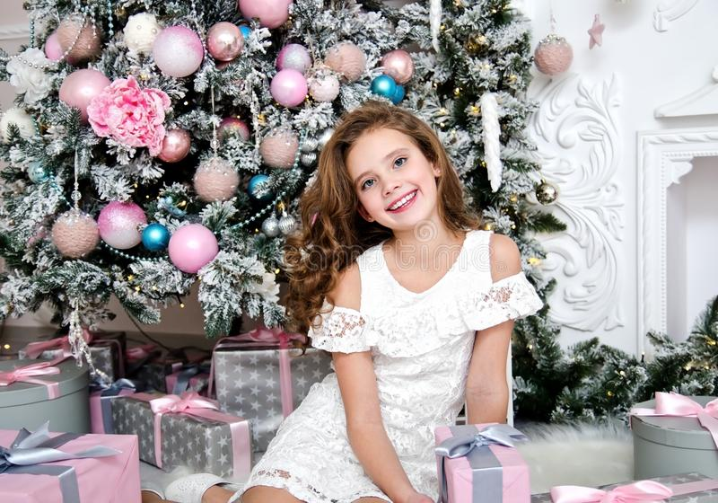 Portrait of adorable happy smiling little girl child in princess dress holding gift box. Sitting near fir tree in christmas time royalty free stock photo
