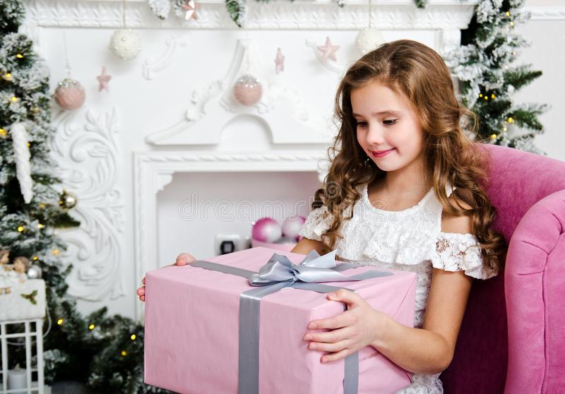 Portrait of adorable happy smiling little girl child in princess dress sitting in the chair with gift box royalty free stock photography