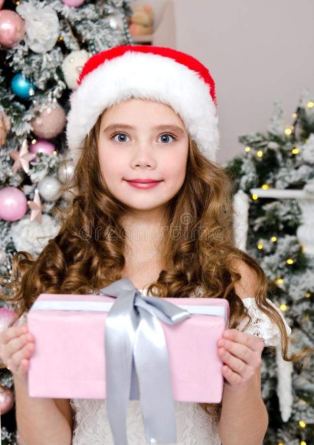Portrait of adorable happy smiling little girl child in santa hat holding gift box near fir tree royalty free stock image
