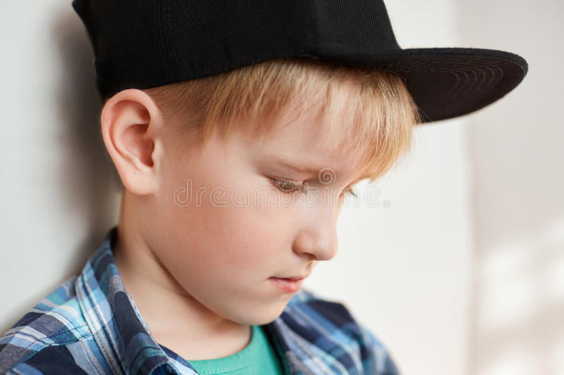 Portrait of adorable little boy with blond hair wearing stylish clothes and cap having thoughtful expression looking down standing stock image