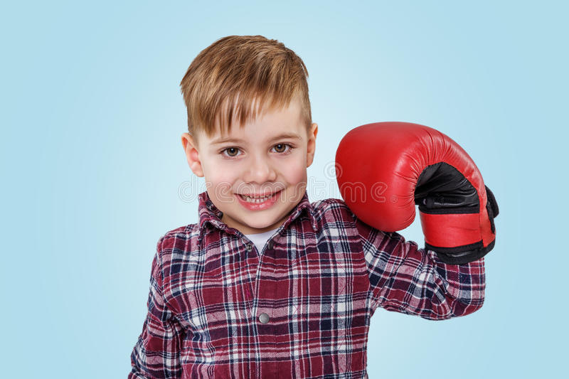 Portrait of an adorable little boy wearing boxing gloves stock image