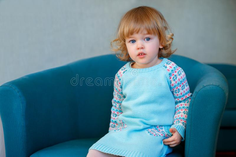 Portrait of adorable little girl with curly blonde hair in casual clothes posing indoors stock images