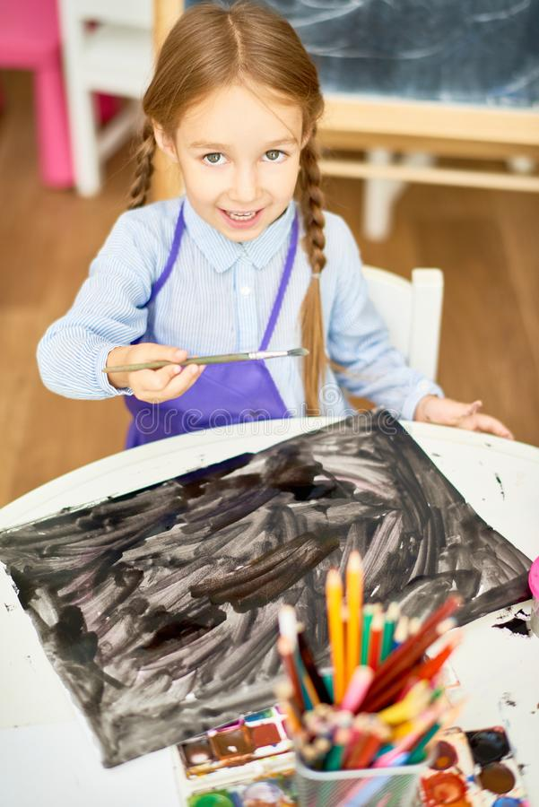 Cute Girl Painting Halloween Pictures in Art Class. Portrait of adorable little girl painting pictures on Halloween enjoying art lesson in development school stock image