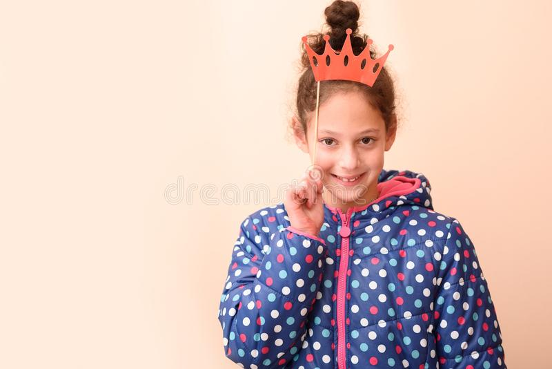 A portrait adorable little girl with princess crown red paper mask at kids birthday party or Purim or fool day party. royalty free stock image
