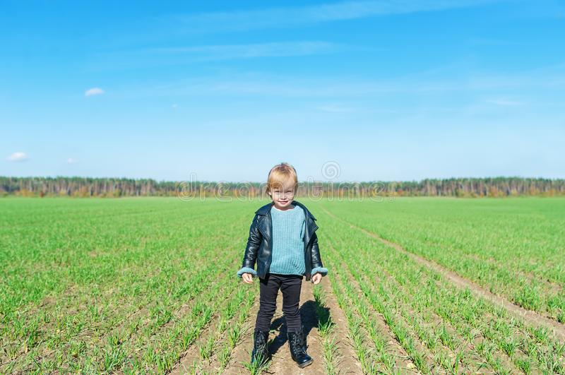 Portrait of adorable little girl standingat farm field. royalty free stock image