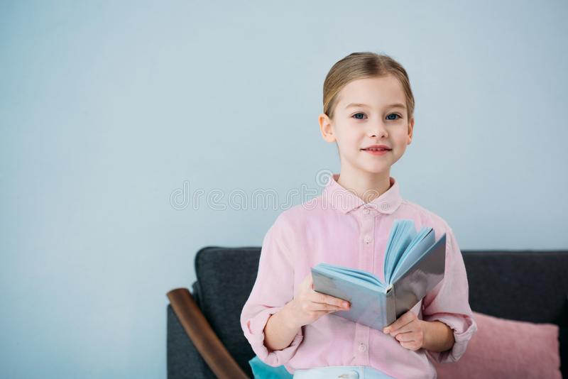 portrait of adorable little kid with book sitting on sofa royalty free stock photography