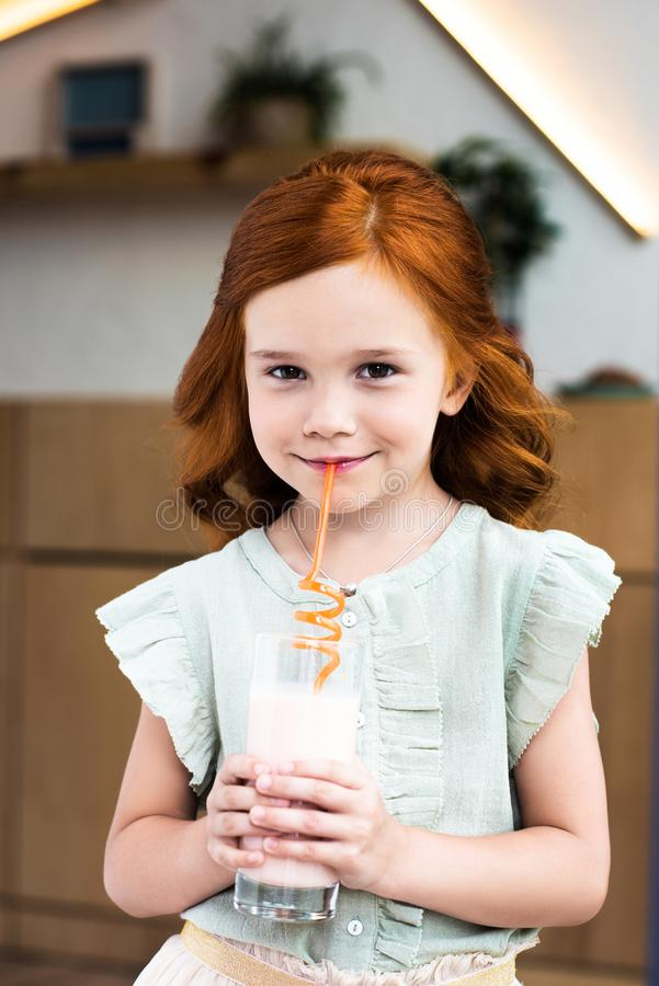 portrait of adorable redhead girl drinking milkshake from glass and smiling royalty free stock images