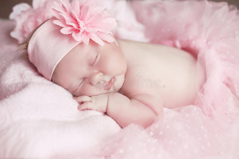 Portrait of adorable sleeping baby girl over pink, infant child. Funny royalty free stock photos