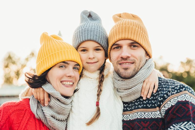 Portrait of adorable small girl wears knitted hat and sweater stands between parents, embrace them. Beautiful woman wears warm sca stock images