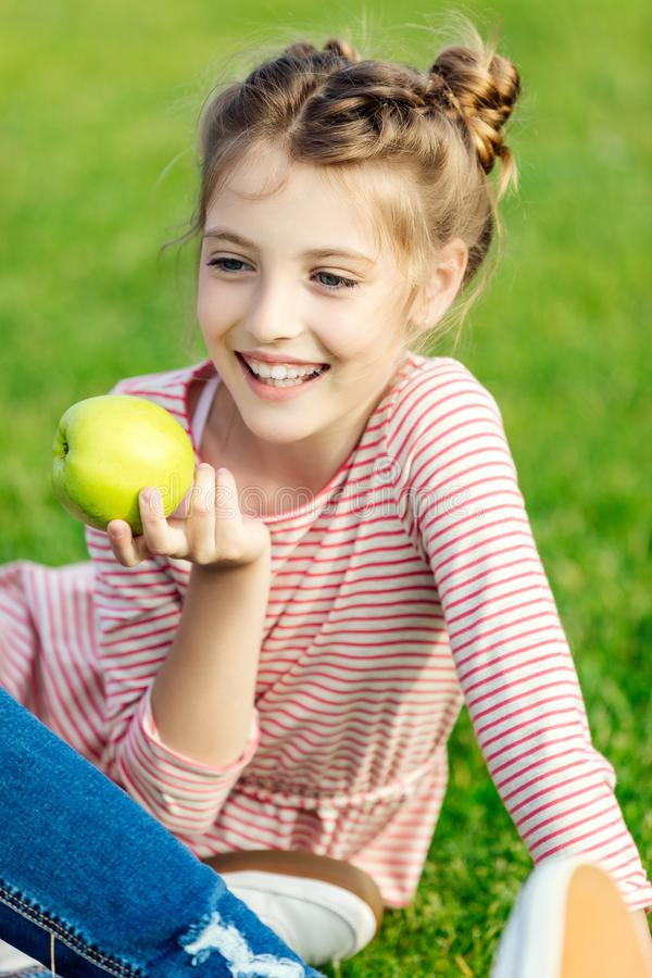 portrait of adorable smiling girl eating green apple while sitting on grass royalty free stock images