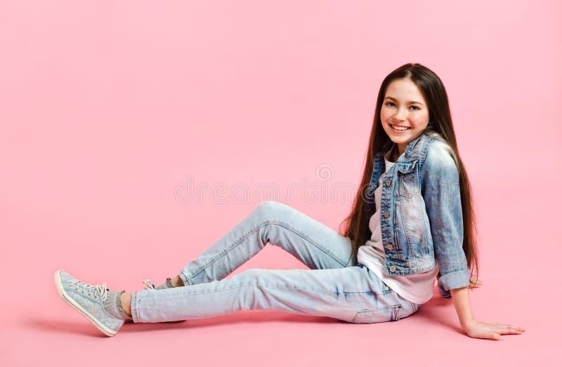 Portrait of adorable smiling little girl child preteen in jeans isolated imagem de stock