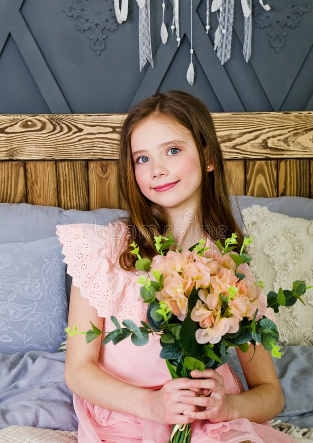 Portrait of adorable smiling little girl child in princess dress sitting on the bed royalty free stock photo