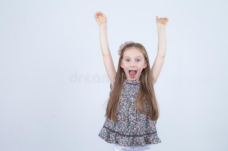 Portrait of adorable smiling little girl isolated on a white. Toddler with her hands up. Happy child. Cheerful and positive emotio. Ns. Happiness and success royalty free stock image