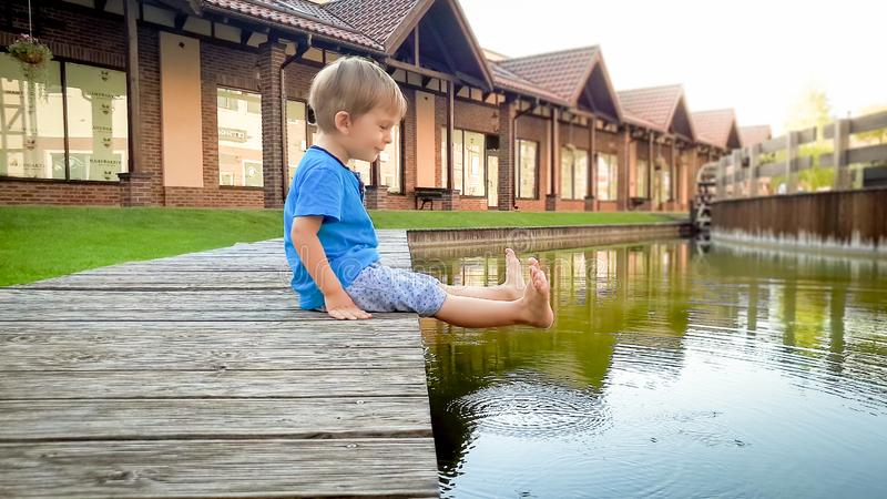 Portrait of adorable smiling toddler boy sitting at river in small town and holding feet in water royalty free stock photo