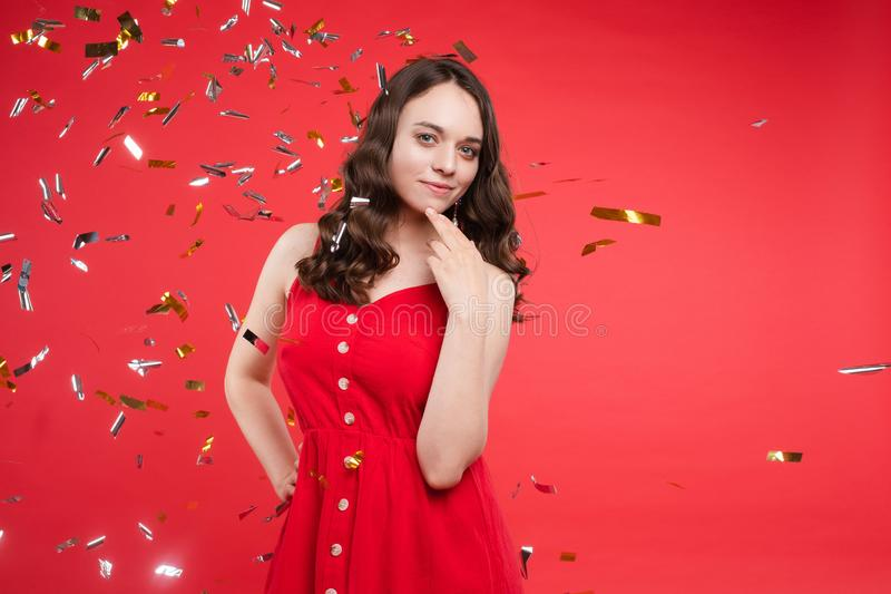 Portrait of adorable smiling young woman with long curly hair posing at red studio background stock photos