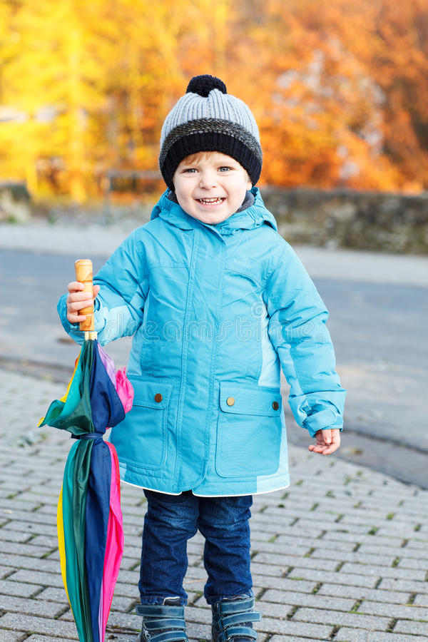 Portrait of adorable toddler boy with blue jacket and colorful u royalty free stock photo