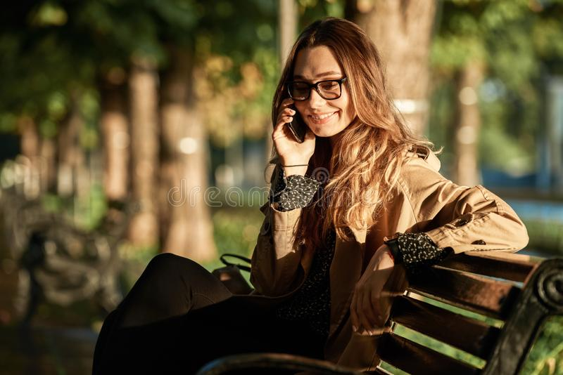 Portrait of adorable woman talking on smartphone while sitting on bench in sunlit alley royalty free stock photography