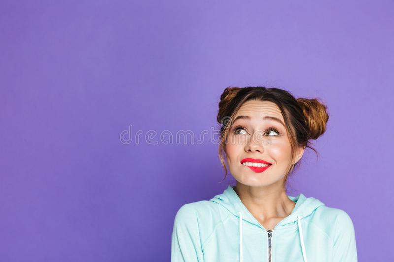 Portrait of adorable woman with two buns looking upward on copyspace and biting lip, isolated over violet background in studio stock photos