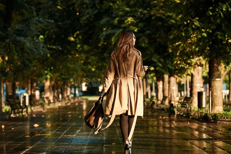 Portrait of adorable woman using mobile phone while walking through empty boulevard royalty free stock photos
