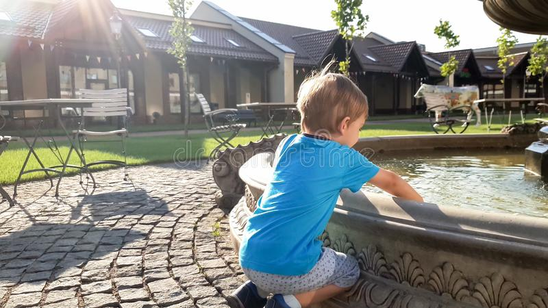 Portrait of adorable 3 years old toddler boy touching water in fountain at park stock photography