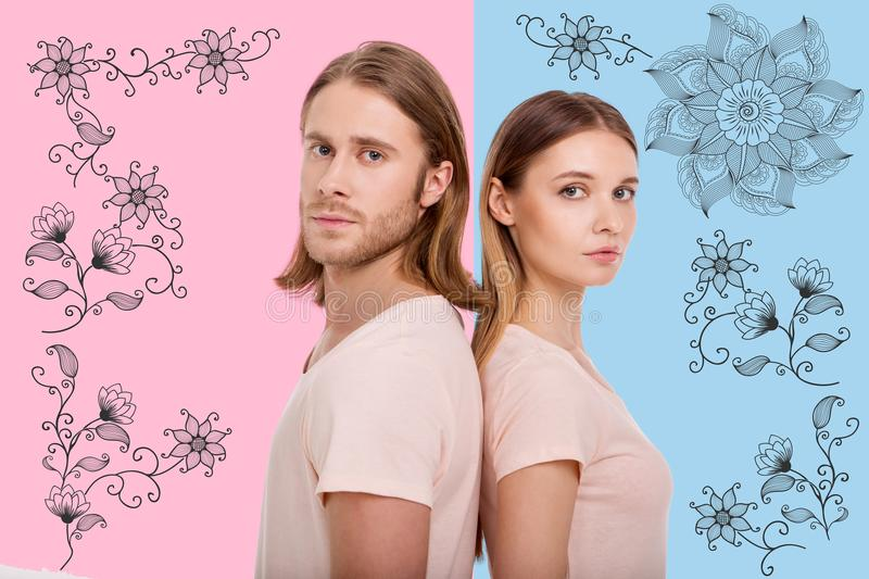 Portrait of adorable young couple against flowery pattern. Faithful relationships. Portrait of young adorable couple standing back to back and looking at you royalty free stock image