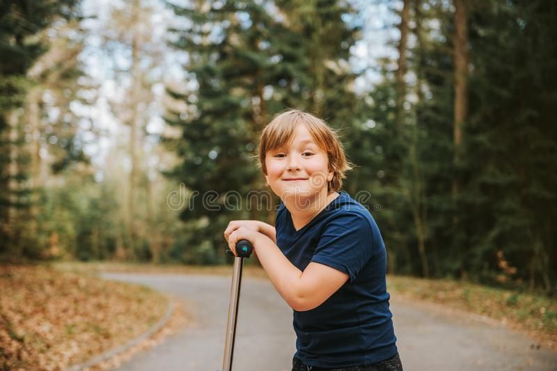 Portrait of adorable young 8 years old blond boy leaning on his scooter royalty free stock images