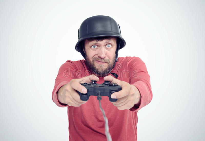 Portrait of adult bearded man in helmet holding joystick and playing videogames. royalty free stock photography