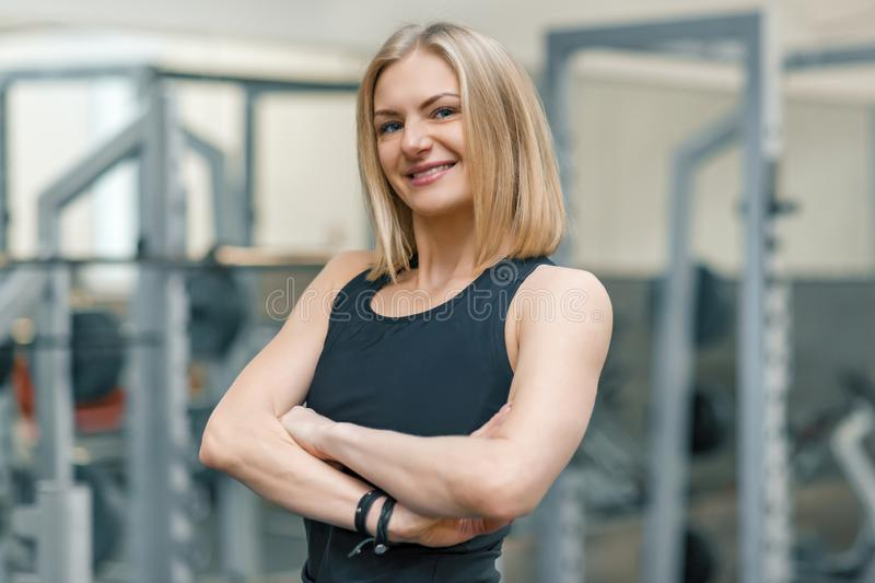Portrait of adult blonde fitness woman personal trainer with folded hands in gym, beautiful smiling female looking in camera royalty free stock photography