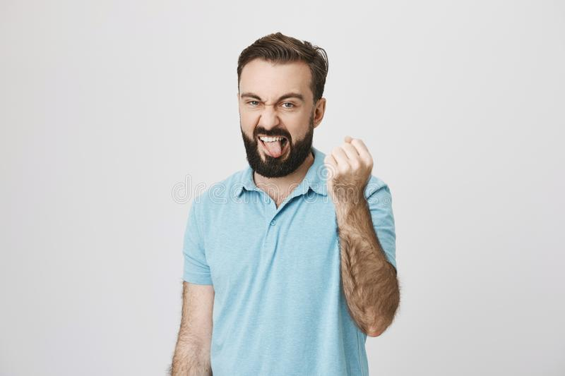Portrait of adult bully, showing his fist and sticking out tongue with annoyed expression, over gray background. Come on stock photography