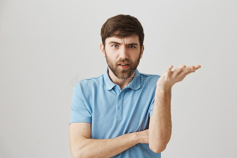 Portrait of adult caucasian guy with beard and moustache, holding raised palm with spread fingers, expressing confusion stock photo