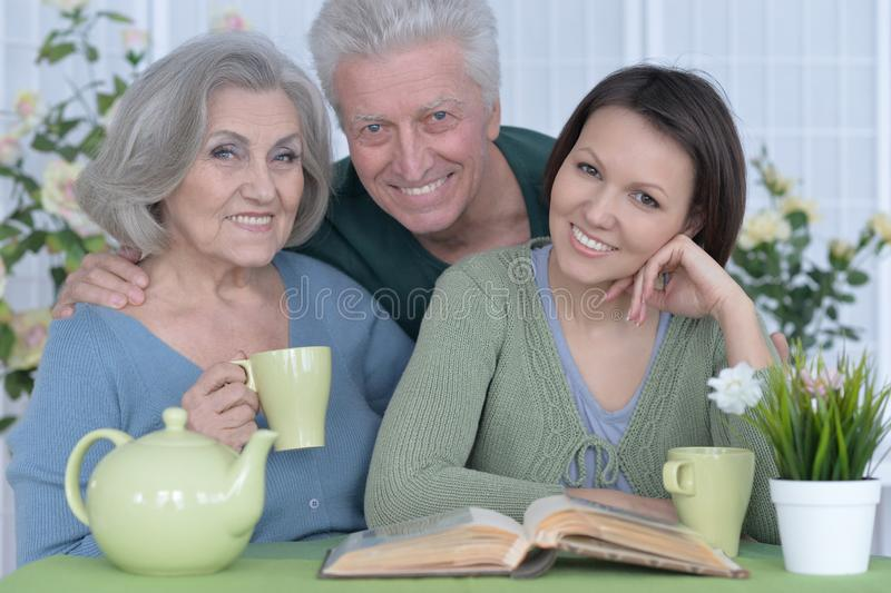 Portrait of adult daughter with senior parents. Cute family portrait, adult daughter with senior parents drinkig tea royalty free stock image