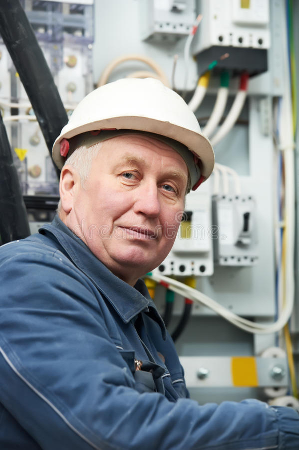 Portrait of adult Electrician. Adult senior electrician portrait at work in front of electrical fusion housing box royalty free stock photography