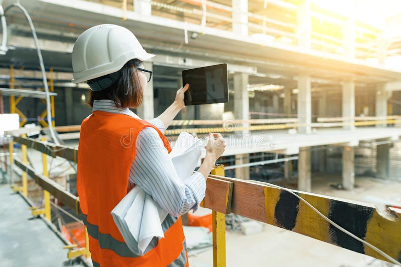 Portrait of adult female builder, engineer, architect, inspector, manager at construction site. Woman makes photo of building royalty free stock image