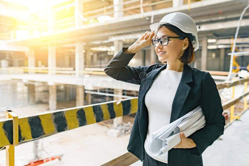 Portrait of adult female builder, engineer, architect, inspector, manager at construction site. Woman with plan, looking at. Building stock photos