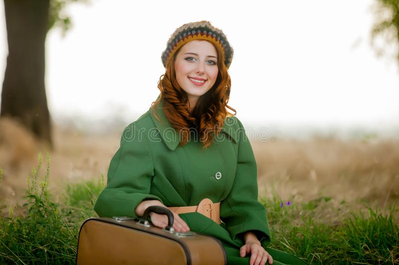Portrait of adult girl in green coat with suitcase. Sitting at grass at countryside outdoor royalty free stock images